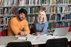 Pares de estudiantes con el ordenador portátil en biblioteca Fotos de archivo