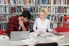 Pares de estudiantes con el ordenador portátil en biblioteca Foto de archivo