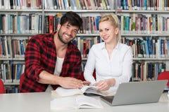 Pares de estudiantes con el ordenador portátil en biblioteca Foto de archivo libre de regalías
