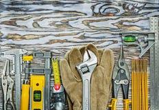 Pares de ferramentas da construção das luvas da segurança na placa de madeira Fotos de Stock