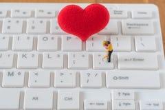 Pares de figura diminuta amante e coração vermelho grande nos comp(s) brancos imagens de stock royalty free