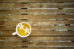 Pares de flores brancas de queda no copo de chá na tabela de madeira Imagem de Stock Royalty Free