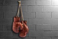 Pares de guantes de boxeo del vintage que cuelgan en una pared Imagen de archivo