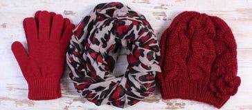Pares de guantes, de casquillo y de mantón de lana para la mujer en viejo fondo de madera Imagen de archivo libre de regalías