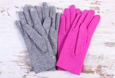 Pares de guantes de lana para la mujer en viejo fondo de madera Foto de archivo libre de regalías