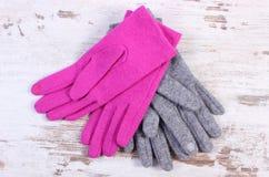 Pares de guantes de lana para la mujer en viejo fondo de madera Imagenes de archivo