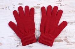Pares de guantes de lana para la mujer en viejo fondo de madera Fotos de archivo libres de regalías