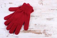 Pares de guantes de lana para la mujer en viejo fondo de madera Fotografía de archivo libre de regalías