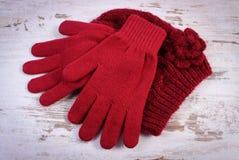 Pares de guantes y de casquillo de lana para la mujer en viejo fondo de madera Foto de archivo
