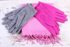 Pares de guantes y de mantón de lana para la mujer en viejo fondo de madera Fotos de archivo libres de regalías