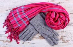 Pares de guantes y de mantón de lana para la mujer en viejo fondo de madera Fotografía de archivo