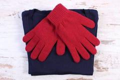 Pares de guantes y de suéter de lana para la mujer en viejo fondo de madera Imagenes de archivo