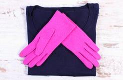 Pares de guantes y de suéter para la mujer en tablero rústico Fotografía de archivo libre de regalías
