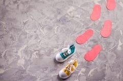 Pares de gumshoes atados coloridos e pegadas vermelhas no cimento cinzento velho com espaço da cópia foto de stock royalty free