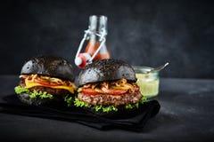 Pares de Hamburger recentemente cozinhados no guardanapo preto imagem de stock