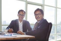 Pares de homem de negócio que trabalham na tabela de funcionamento do escritório com SMI Fotos de Stock