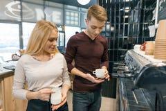 Pares de homem novo e de proprietários de cafetaria fêmeas perto do contador, falando e sorrindo, conceito do negócio da cafetari imagem de stock royalty free