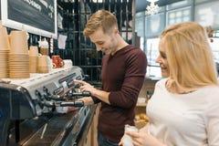Pares de homem novo e de proprietários de cafetaria fêmeas perto do contador, falando e sorrindo, conceito do negócio da cafetari imagens de stock royalty free