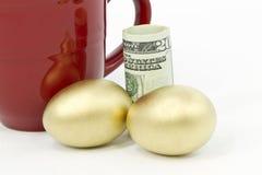 Pares de huevos del oro, de dinero en circulación del dólar, y de taza roja Foto de archivo libre de regalías