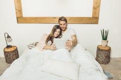 Pares de indivíduo e de menina na cama que olham uma tabuleta fotografia de stock
