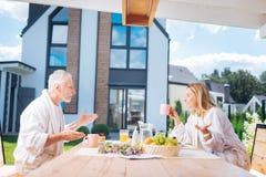 Pares de irradiação felizes que têm a conversação emocional ao comer seu café da manhã fotos de stock