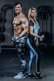 Pares de la aptitud - mujer y hombre con pesas de gimnasia en gimnasio Imágenes de archivo libres de regalías