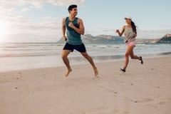 Pares de la aptitud que corren en la playa Imágenes de archivo libres de regalías