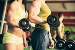 Pares de la aptitud que se resuelven en gimnasio con pesas de gimnasia Foto de archivo