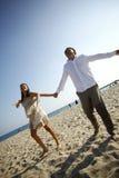Pares de la boda con los brazos abiertos de par en par en la playa Imagen de archivo libre de regalías