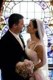 Pares de la boda delante de la ventana de cristal manchada Foto de archivo