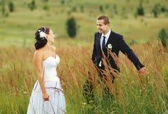 Pares de la boda en campo Imagenes de archivo