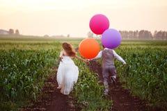 Pares de la boda en el campo con los globos grandes Imagen de archivo libre de regalías