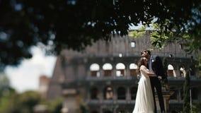 Pares de la boda en Roma que presenta cerca del coliseo Novia hermosa que se inclina al hombro de su nuevo marido Luna de miel ad almacen de video