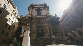 Pares de la boda en Roma que se besa cerca de la iglesia de San Nicola da Tolentino Novia hermosa y del novio ebraces elegantes s metrajes