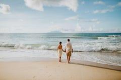 Pares de la boda de la luna de miel en la playa en la puesta del sol fotos de archivo libres de regalías