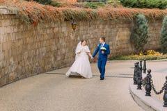 Pares de la boda, novia alegre y novio cariñoso dando un paseo en parque cerca de la pared de la piedra arenisca Imagenes de archivo