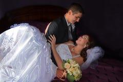 Pares de la boda Novia encantadora y novio que se sientan en una cama Imagen de archivo libre de regalías