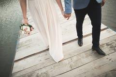 Pares de la boda, novia, novio que camina y que presenta en el embarcadero fotografía de archivo