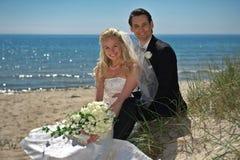 Pares de la boda por el mar Imagenes de archivo