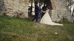 Pares de la boda que abrazan antes de pared vieja de la roca almacen de metraje de vídeo