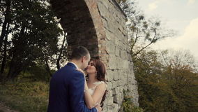 Pares de la boda que abrazan antes de pared vieja de la roca metrajes