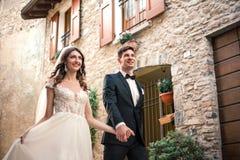 Pares de la boda que caminan abajo de una calle Fotos de archivo