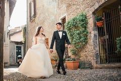 Pares de la boda que caminan abajo de una calle Imágenes de archivo libres de regalías