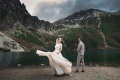 Pares de la boda que caminan cerca del lago en las monta?as de Tatra en Polonia Morskie Oko D?a de verano hermoso fotos de archivo libres de regalías