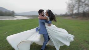 Pares de la boda que corren cerca del río de la montaña Novio y novia en amor almacen de video