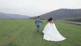 Pares de la boda que corren cerca del río de la montaña Novio y novia en amor metrajes