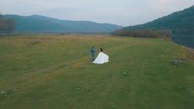 Pares de la boda que corren cerca del río de la montaña Novio y novia Opinión de Arial metrajes