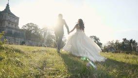 Pares de la boda que corren en campo de hierba cerca de castillo en puesta del sol