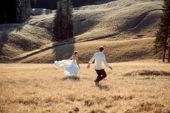 Pares de la boda que corren en el campo Día asoleado en montañas Imagenes de archivo