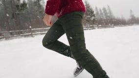 Pares de la boda que corren en invierno nevoso durante las nevadas Tiro del ángulo bajo de pies en las botas de cuero que caminan almacen de video